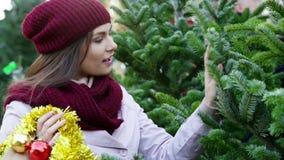 γυναίκα που μένει μεταξύ των χριστουγεννιάτικων δέντρων απόθεμα βίντεο