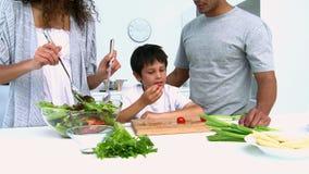 Γυναίκα που μαγειρεύει μια σαλάτα με το γιο της απόθεμα βίντεο