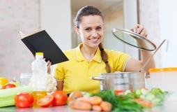 Γυναίκα που μαγειρεύει τα χορτοφάγα τρόφιμα με το cookbook στοκ εικόνες με δικαίωμα ελεύθερης χρήσης