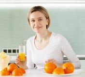 Γυναίκα που μαγειρεύει το χυμό από πορτοκάλι στο juicer Στοκ Εικόνες