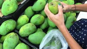 Γυναίκα που μαζεύει με το χέρι το φρέσκο οργανικό μάγκο στην υπεραγορά αγορές τροφίμων απόθεμα βίντεο