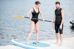 Γυναίκα που μαθαίνει να κάνει σερφ σε ένα paddleboard με τον εκπαιδευτικό στοκ εικόνα με δικαίωμα ελεύθερης χρήσης