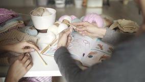 Γυναίκα που μαθαίνει να πλέκει τη χρησιμοποίηση του βιβλίου με το πλέξιμο του σχεδίου πλέξιμο χεριών φιλμ μικρού μήκους