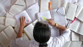 Γυναίκα που μελετά μπροστά από πολλά βιβλία απόθεμα βίντεο