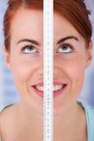 Γυναίκα που μετρά το ύψος με την ταινία μέτρου Στοκ Εικόνα