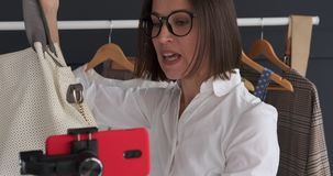 Γυναίκα που μιλά για τη νέα εξάρτηση και που παρουσιάζει καθιερώνουσα τη μόδα τσάντα vlogging φιλμ μικρού μήκους
