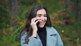 Γυναίκα που μιλά σε ένα κινητό τηλέφωνο κυττάρων στο πάρκο κοντά επάνω απόθεμα βίντεο