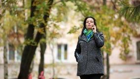 Γυναίκα που μιλά σε ένα τηλέφωνο mobilecell στο πάρκο απόθεμα βίντεο