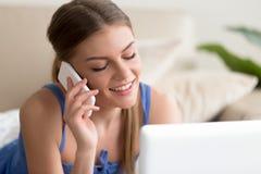 Γυναίκα που μιλά στο κινητό τηλέφωνο χρησιμοποιώντας το lap-top Στοκ φωτογραφία με δικαίωμα ελεύθερης χρήσης