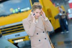 Γυναίκα που μιλά στο τηλέφωνο κοντά στο φορτηγό ρυμούλκησης Στοκ εικόνες με δικαίωμα ελεύθερης χρήσης