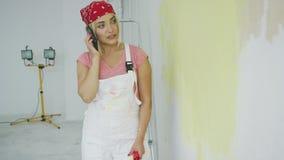 Γυναίκα που μιλά στο smartphone στον μισό-χρωματισμένο τοίχο απόθεμα βίντεο