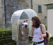 Γυναίκα που μιλά σε έναν τηλεφωνικό θάλαμο Στοκ Εικόνες