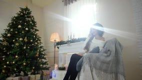 Γυναίκα που μιλά σε ένα κινητό τηλέφωνο σε μια άνετη ατμόσφαιρα, σε έναν αναδρομικά φωτισμένο, καθμένος στον καναπέ, κοντά στο χρ απόθεμα βίντεο