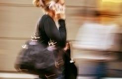 Γυναίκα που μιλά σε ένα τηλέφωνο κυττάρων σε μια βιασύνη στοκ εικόνες