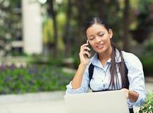 Γυναίκα που μιλά σε ένα τηλέφωνο, που κοιτάζει στην οθόνη lap-top Στοκ Εικόνες
