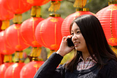 Γυναίκα που μιλά στο τηλέφωνο κυττάρων κατά τη διάρκεια του κινεζικού νέου έτους Στοκ εικόνες με δικαίωμα ελεύθερης χρήσης