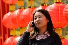 Γυναίκα που μιλά στο τηλέφωνο κυττάρων κατά τη διάρκεια του κινεζικού νέου έτους Στοκ φωτογραφία με δικαίωμα ελεύθερης χρήσης