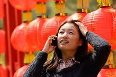 Γυναίκα που μιλά στο τηλέφωνο κυττάρων κατά τη διάρκεια του κινεζικού νέου έτους Στοκ Εικόνες