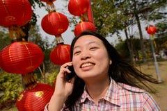 Γυναίκα που μιλά στο τηλέφωνο κυττάρων κατά τη διάρκεια του κινεζικού νέου έτους Στοκ Εικόνα