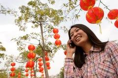 Γυναίκα που μιλά στο τηλέφωνο κυττάρων κατά τη διάρκεια του κινεζικού νέου έτους Στοκ Φωτογραφία