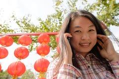 Γυναίκα που μιλά στο τηλέφωνο κυττάρων κατά τη διάρκεια του κινεζικού νέου έτους Στοκ Φωτογραφίες