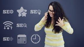 Γυναίκα που μιλά στο τηλέφωνο μπροστά από το υπόβαθρο με τα συρμένα επιχειρησιακά διαγράμματα Στοκ Εικόνα