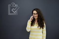 Γυναίκα που μιλά στο τηλέφωνο μπροστά από το υπόβαθρο με τα συρμένα επιχειρησιακά διαγράμματα Στοκ Φωτογραφίες