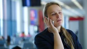 Γυναίκα που μιλά στο τηλέφωνο στη αίθουσα αναμονής απόθεμα βίντεο