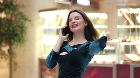 Γυναίκα που μιλά στο τηλέφωνο στη λεωφόρο αγορών απόθεμα βίντεο