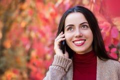Γυναίκα που μιλά στο τηλέφωνο στο πάρκο φθινοπώρου Στοκ Εικόνες