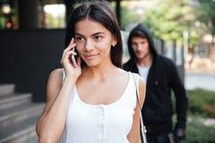 Γυναίκα που μιλά τηλέφωνο και που καταδιώκει στο κινητό από τον εγκληματία ανδρών Στοκ Φωτογραφία