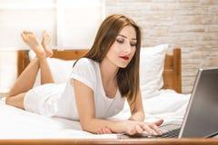 Γυναίκα που ξαπλώνει το κρεβάτι μπροστά από το lap-top της Στοκ εικόνες με δικαίωμα ελεύθερης χρήσης