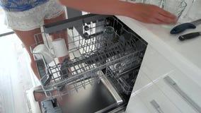 Γυναίκα που ξεφορτώνει το πλυντήριο πιάτων στο σπίτι απόθεμα βίντεο