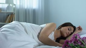 Γυναίκα που ξυπνά στο κρεβάτι για να δει την ανθοδέσμη των όμορφων λουλουδιών, ευχάριστη έκπληξη φιλμ μικρού μήκους