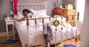 Γυναίκα που ξυπνιέται από τον κινητό τηλεφωνικό συναγερμό πριν από να ξεπεράσει το κρεβάτι απόθεμα βίντεο