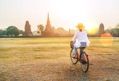 Γυναίκα που οδηγά bicykle κοντά στο ιστορικό πάρκο Ayutthaya στην Ταϊλάνδη, χρόνος ξημερωμάτων στοκ φωτογραφίες με δικαίωμα ελεύθερης χρήσης