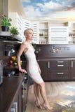 Γυναίκα που ονειρεύεται για τις διακοπές της στη σύγχρονη κουζίνα Στοκ Εικόνες