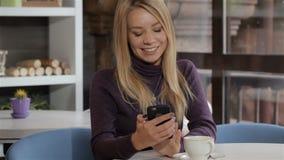Γυναίκα που ονειρεύεται με το smartphone στο χέρι της στον καφέ απόθεμα βίντεο