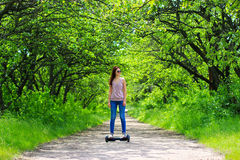 Γυναίκα που οδηγά ένα ηλεκτρικό μηχανικό δίκυκλο υπαίθρια - αιωρηθείτε τον πίνακα, έξυπνη ρόδα ισορροπίας, μηχανικό δίκυκλο γυροσ Στοκ Φωτογραφία