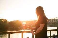 Γυναίκα που πίνει ένα κρασί στην πόλη κατά τη διάρκεια ενός ηλιοβασιλέματος κόκκινο κρασί γυαλιού Έννοια του ελεύθερου χρόνου στη Στοκ Εικόνα