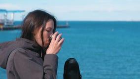 Γυναίκα που πίνει ένα τσάι από thermos στην προκυμαία Νέο brunette σε ένα ταξίδι απόθεμα βίντεο