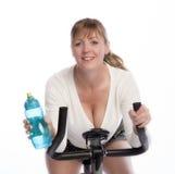 Γυναίκα που πίνει και που οδηγά ένα ποδήλατο άσκησης στοκ φωτογραφία