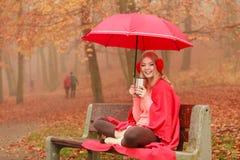 Γυναίκα που πίνει την καυτή χαλάρωση καφέ στο πάρκο φθινοπώρου στοκ φωτογραφίες