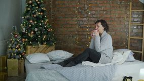 Γυναίκα που πίνει το καυτό τσάι κοντά στο χριστουγεννιάτικο δέντρο απόθεμα βίντεο