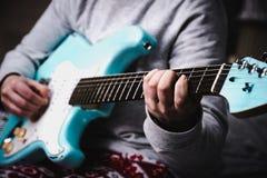 Γυναίκα που παίζει την μπλε ηλεκτρική κιθάρα κοντά επάνω στο σπίτι Κιθάρα άσκησης στοκ φωτογραφία
