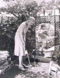 Γυναίκα που παίζει το μικροσκοπικό γκολφ Στοκ Φωτογραφία