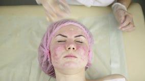 Γυναίκα που παίρνει μια καλλυντική επεξεργασία ιατρικής, καθαρίζοντας το δέρμα προσώπου με τη μάσκα απόθεμα βίντεο