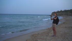 Γυναίκα που παίρνει μια φωτογραφία μιας θάλασσας στο έξυπνο τηλέφωνο στο ηλιοβασίλεμα φιλμ μικρού μήκους