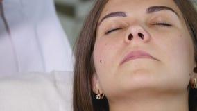Γυναίκα που παίρνει την RF-ανύψωση σε ένα σαλόνι ομορφιάς Γυναίκα που έχει μια παρακινητική του προσώπου επεξεργασία Υγιές κορίτσ απόθεμα βίντεο