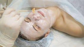 Γυναίκα που παίρνει τη μάσκα αποφλοίωσης προσώπου στο σαλόνι ομορφιάς SPA απόθεμα βίντεο